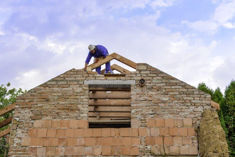 Litovel, republika czech Sierpień 3th 2018, budowniczy pozycja na dachowej szalunek budowie i apretura ceglany szczyt, obrazy stock