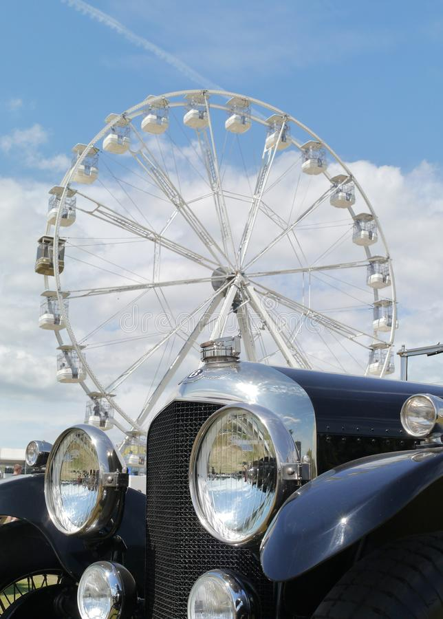 Bently antique car and big wheel at Goodwood Festival of Speed. 8 Litre blue pre war Bentley old motorcar at Goodwood Festival of Speed. A white ferris wheel in stock photo