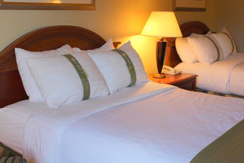 Lits confortables mous dans la chambre d'hôtel de accueil photographie stock libre de droits