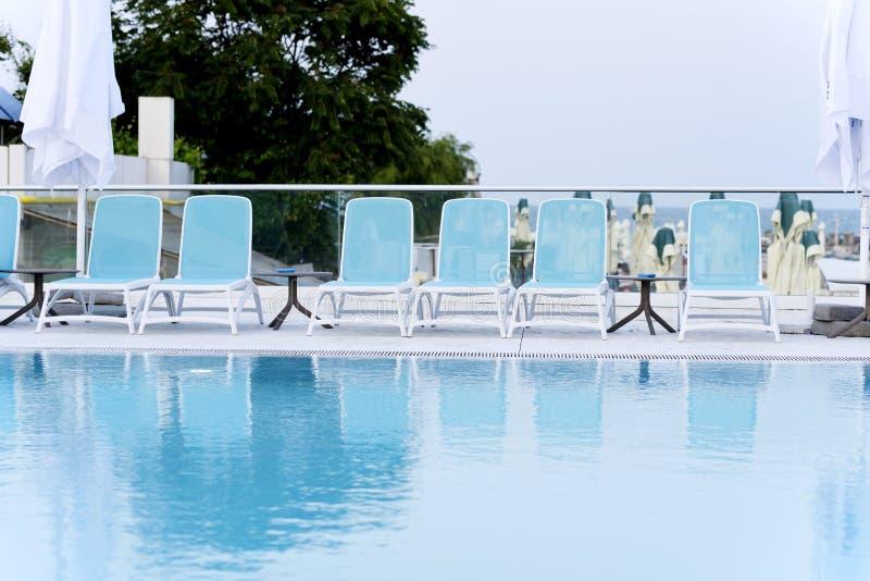Lits pliants avec la vue de piscine photos stock