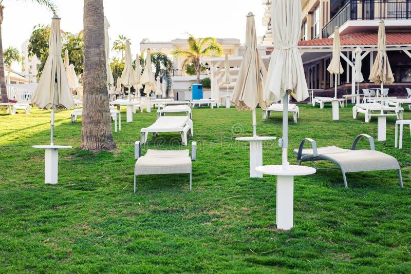 Lits pliants blancs dans le jardin du ` s d'hôtel Vacances d'été, hôtel et concept de station thermale photographie stock