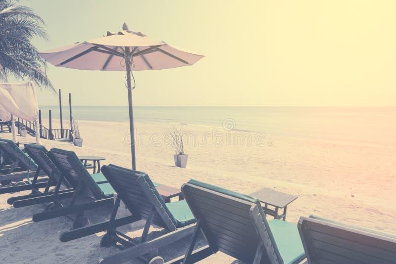 Lits pliants et parasol, chaise de plage de parapluie sur la plage Couleur de filtre de vintage images stock