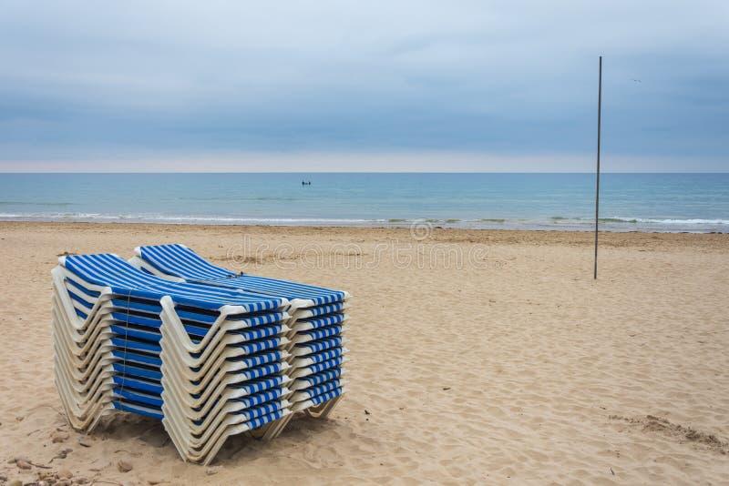 Lits pliants rayés bleus et blancs empilés sur la plage avec la mer à l'arrière-plan un après-midi nuageux d'été photographie stock libre de droits