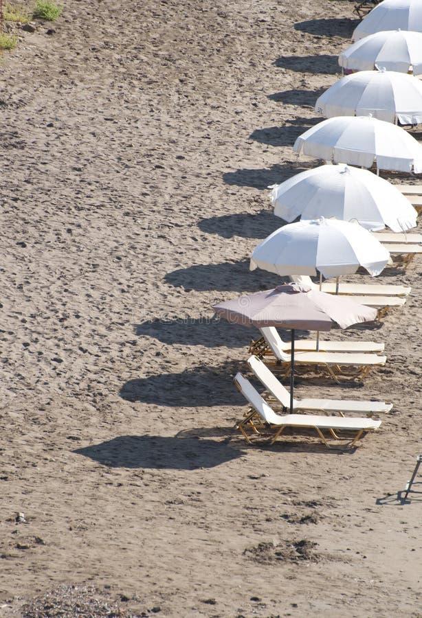 Lits pliants sur la plage dans la rang?e images stock