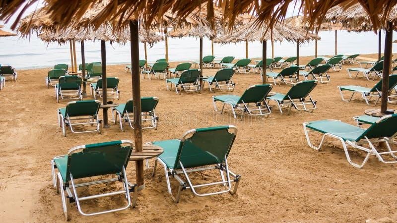 Lits pliants verts et parapluies faits de roseau sur une plage photos libres de droits