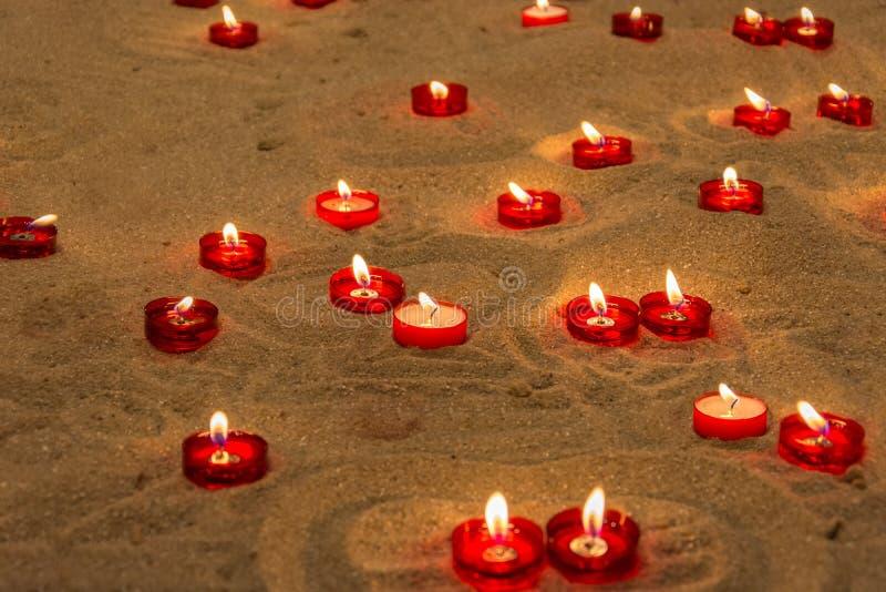 Litstearinljus på sand i en kyrka som ska bes för folk som dog royaltyfri foto