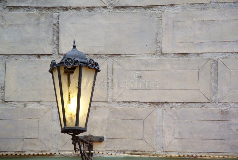 Litstraßen-Antikenlampe auf der Backsteinmauer tagsüber stockbild