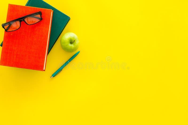 Littérature éducative Manuel scolaire, livre, cours, pomme et verres sur l'espace jaune de copie de vue supérieure de fond photographie stock libre de droits