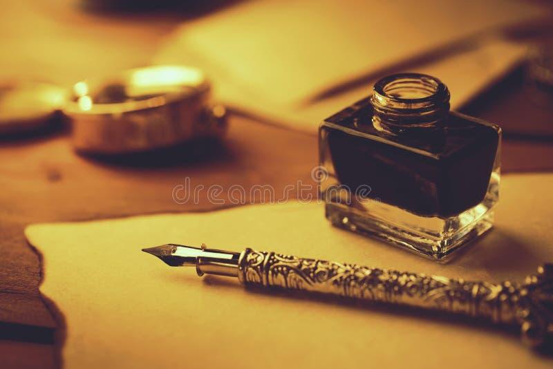 littérature de cru - rétro stylo et encrier encastré de plume sur le vieux parchemin photographie stock