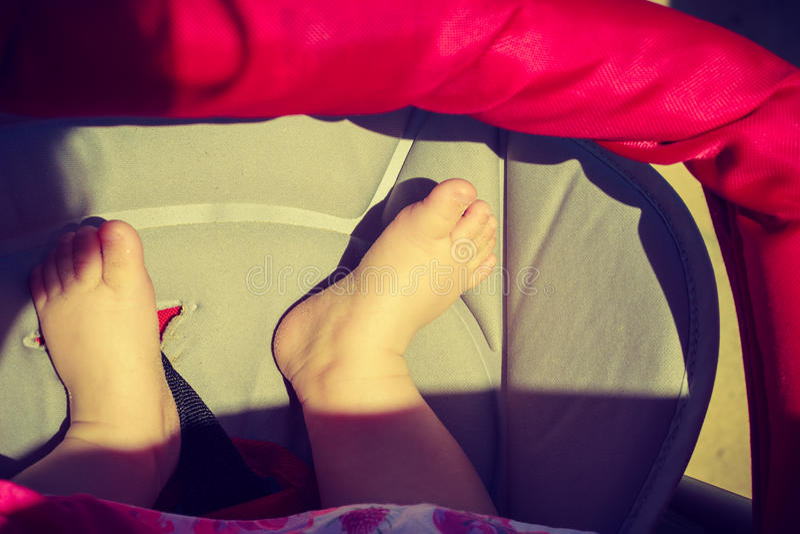 Litte baby feet in pram in sunlight stock photos