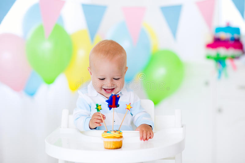 Litte boy celebrating first birthday. Adorable baby boy celebrating first birthday blowing candles on colorful cup cake. Kids birthday party decorated with stock images