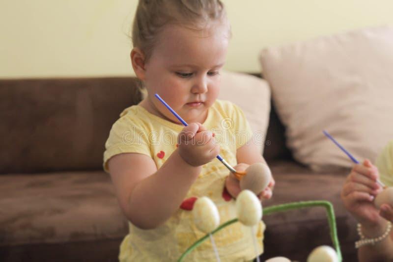 Litte dziewczyna maluje Easter jajka zdjęcie stock