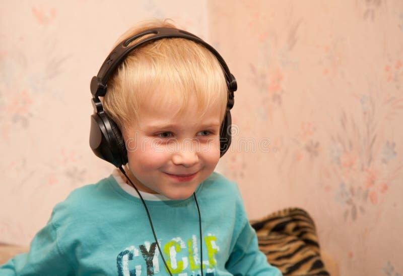 littening音乐的男孩耳机 免版税库存照片