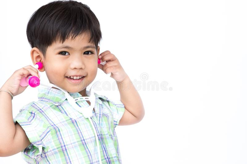 The litter boy is wearing the stethoscope. The litter boy is wearing the stethoscope and one hand is holding injection needle, with isolate white background stock image