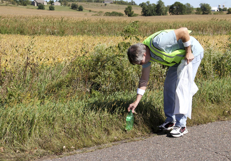 Litter Clean Up. Highway worker picking up litter along a roadside royalty free stock image