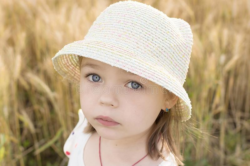 Litter girl in thatch hat on the wheat field background royalty free stock photos
