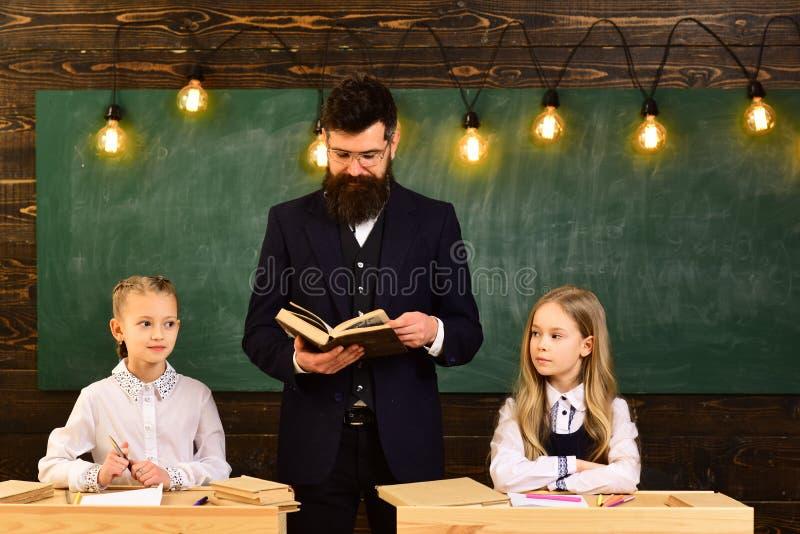 litteratur litteraturkurs för två lilla flickor med den allvarliga läraremannen Litteratur och grammatik skolakurs av royaltyfri fotografi