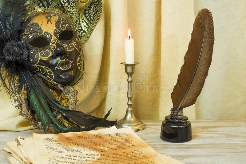 Litteraturbegrepp, stearinljus i en ljusstake nära en Venetian maskering arkivbild