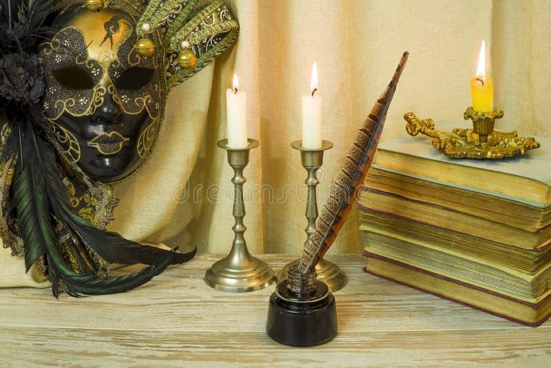 Litteraturbegrepp, stearinljus i en ljusstake nära en Venetian maskering royaltyfri fotografi