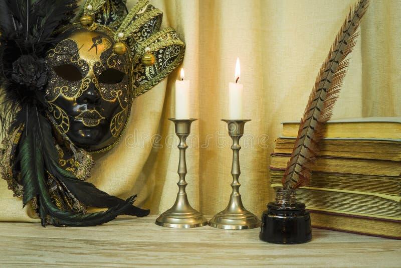 Litteraturbegrepp, stearinljus i en ljusstake nära en Venetian maskering royaltyfria foton