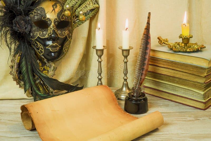Litteraturbegrepp, stearinljus i en ljusstake nära en Venetian maskering fotografering för bildbyråer
