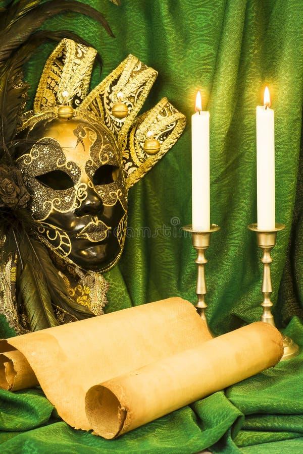 Litteraturbegrepp, stearinljus i en ljusstake nära en Venetian maskering arkivfoton