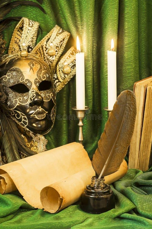Litteraturbegrepp, stearinljus i en ljusstake nära en Venetian maskering royaltyfria bilder