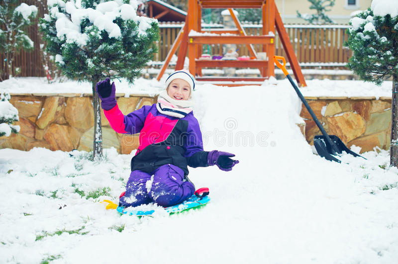 Little active happy girl riding on slade on ice and snow hill royalty free stock images