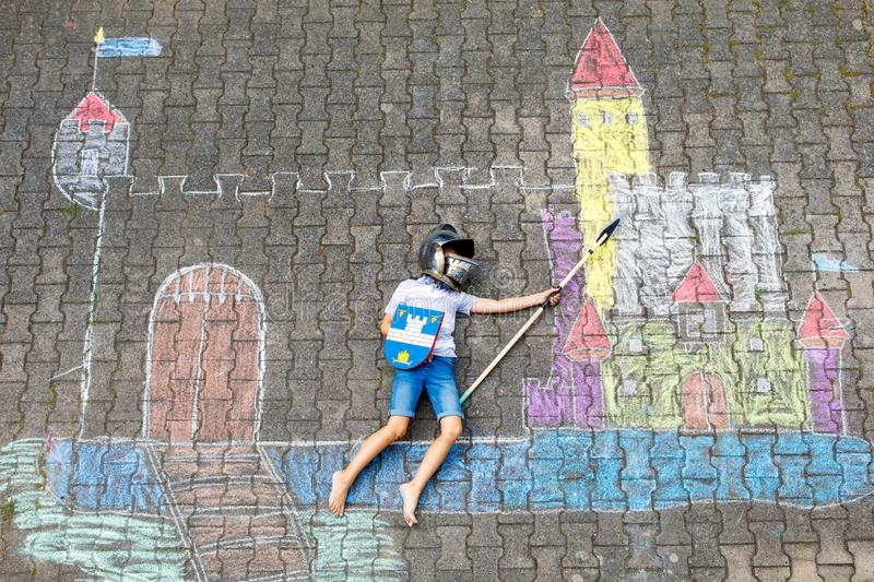 Little active kid boy drawing knight castle and fortress with colorful chalks on asphalt. Happy child in helmet and with royalty free stock images