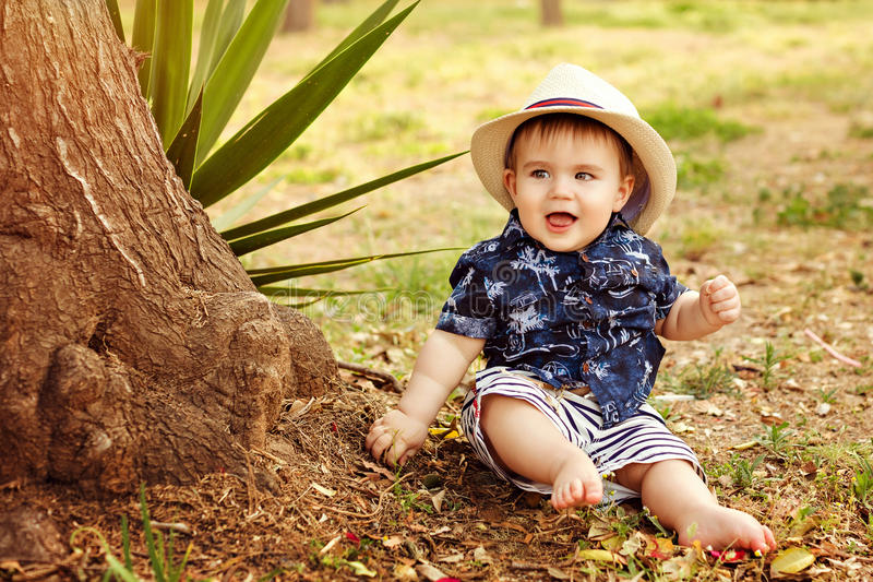 Little adorable baby boy in a straw hat and blue shirt sitting s royalty free stock image