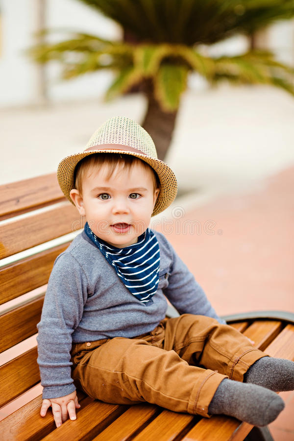 Little adorable baby boy in a straw hat and brown pants sitting. On the bench amid palm trees and smiling, summer stock photo