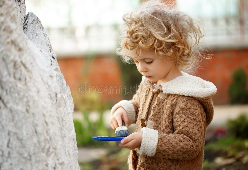 Little adorable blonde girl covering the tree with white paint to protect against rodents in the garden in the spring. royalty free stock photos