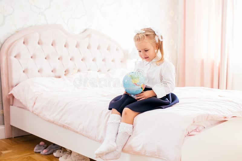 Little adorable blonde girl in school uniform and white golfs siting on a ber in her bedroom with globe in her hands stock photos