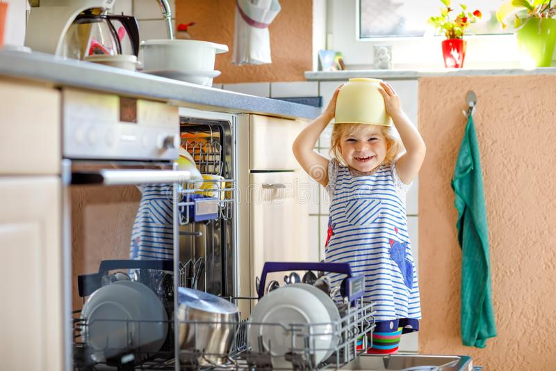Little adorable child helping to unload dishwasher. Funny happy toddler girl standing in the kitchen, holding dishes and stock images