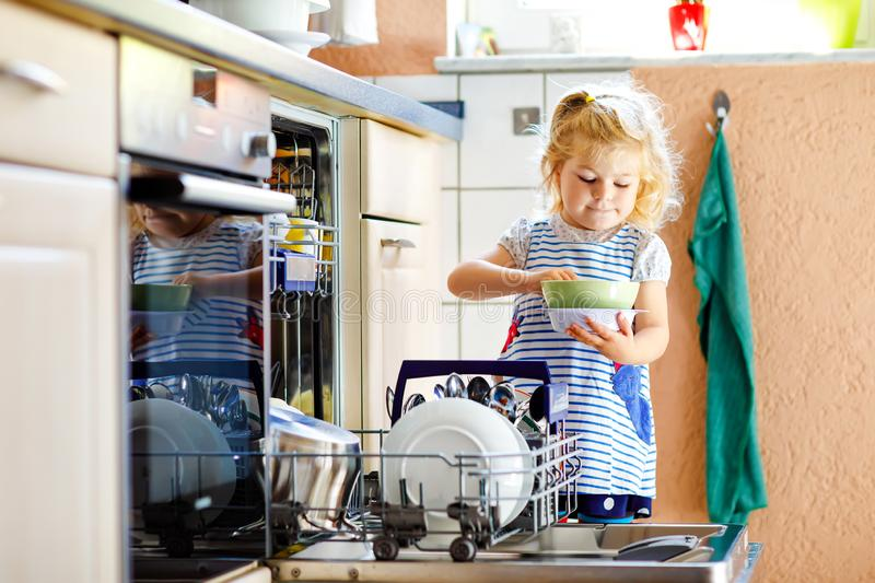 Little adorable cute toddler girl helping to unload dishwasher. Funny happy child standing in the kitchen, holding royalty free stock images