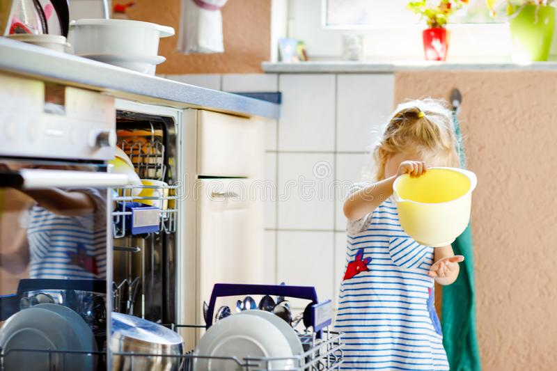 Little adorable cute toddler girl helping to unload dishwasher. Funny happy child standing in the kitchen, holding royalty free stock image