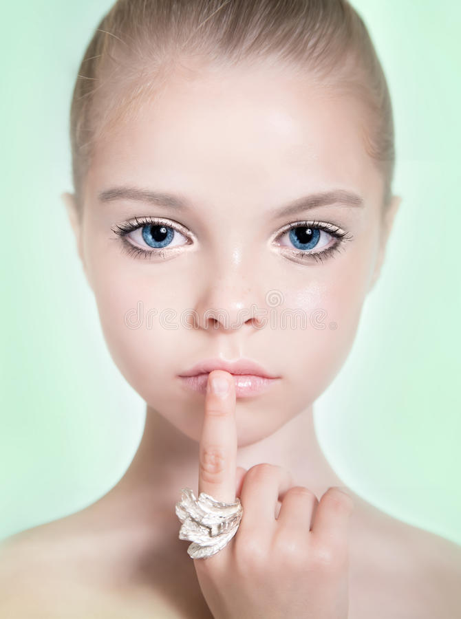 Little adorable fashion eight-year model girl with with a profe. Ssional makeup and jewelry. Beauty make up stock photos