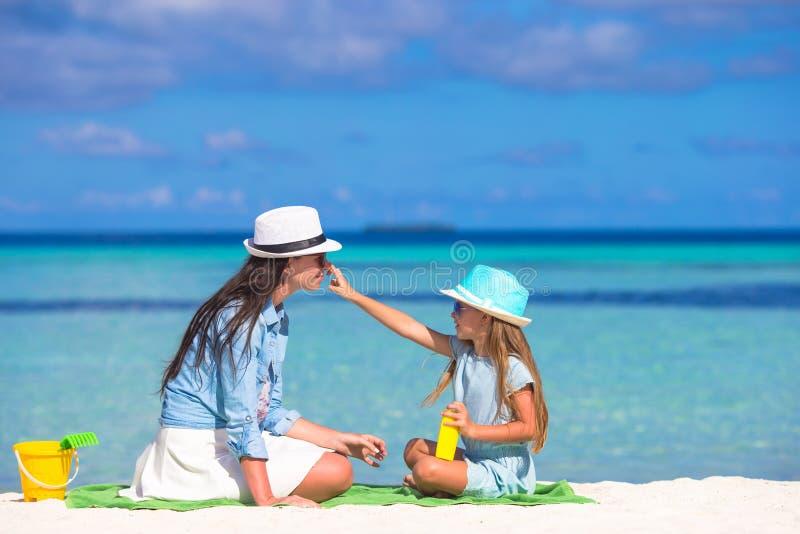 Little adorable girl applying sun cream to her stock photography