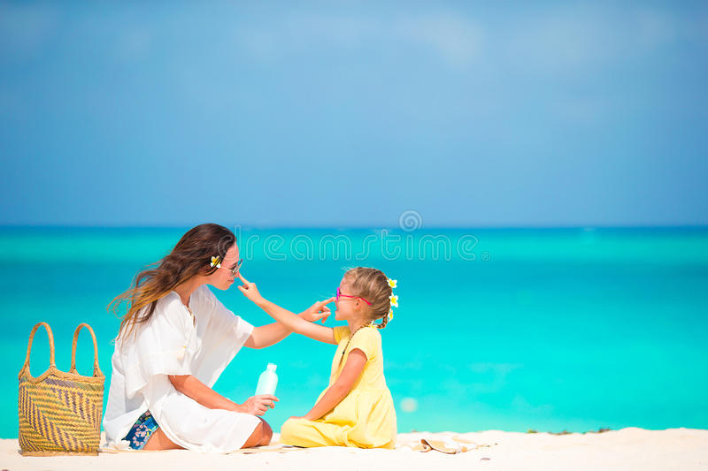 Little adorable girl applying sun cream to her mother nose. Little daughter applying sun cream to her mother nose royalty free stock images
