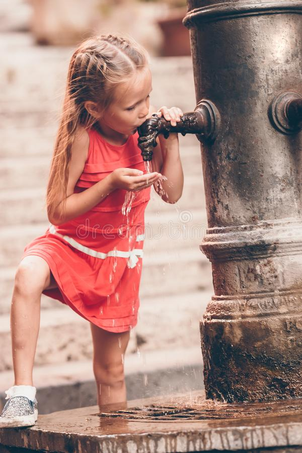 Little girl having fun with drinking water at street fountain in Rome, Italy royalty free stock photography