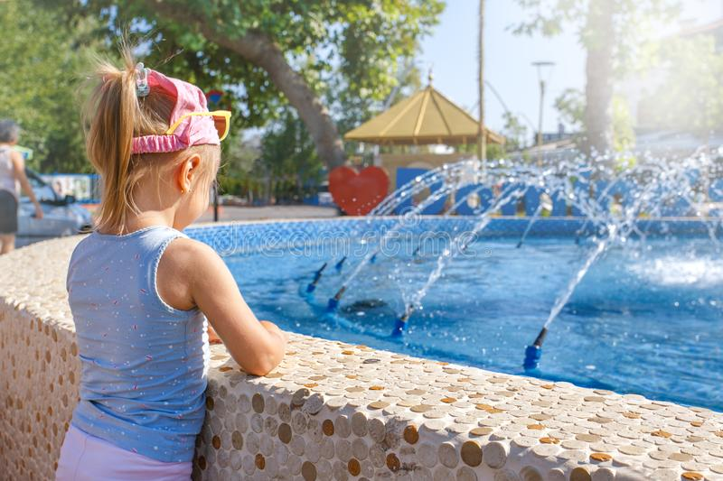 Little adorable girl have fun in street fountain at sunny day. royalty free stock photography