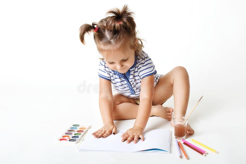 Little adorable girl preschooler with painted hands, makes fingerprints on blank page of album, uses watercolor for making royalty free stock photography