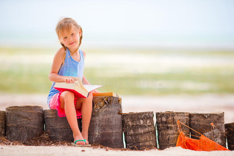 Little adorable girl reading book during tropical white beach royalty free stock photography