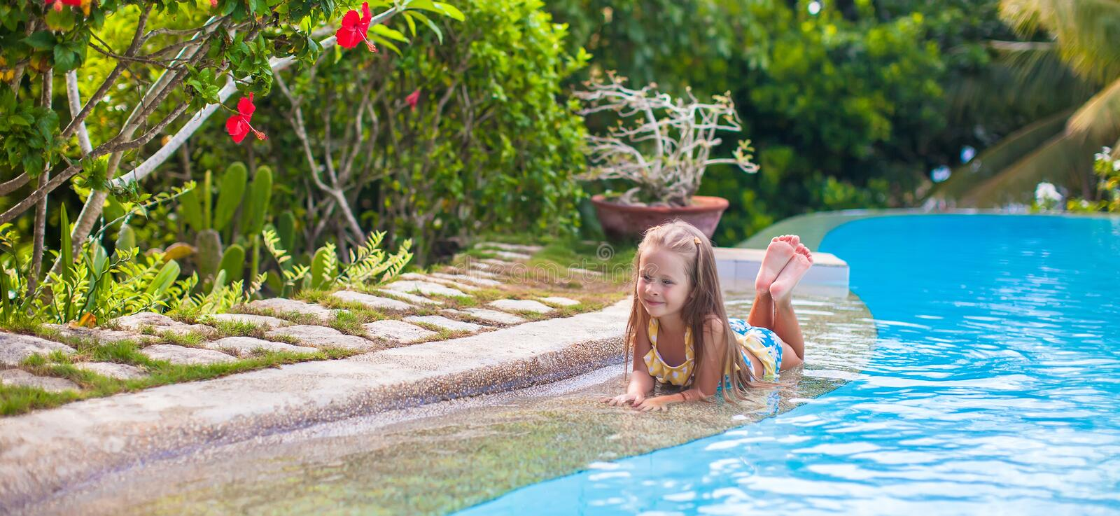 Little adorable girl in swimming pool relax. Little adorable girl in the swimming pool looks at camera royalty free stock image