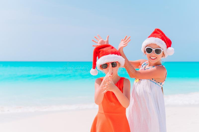 Little adorable girls in Santa hats during beach Christmas vacation having fun together. Little adorable girls in Santa hats having fun anad fooling at Christmas royalty free stock image