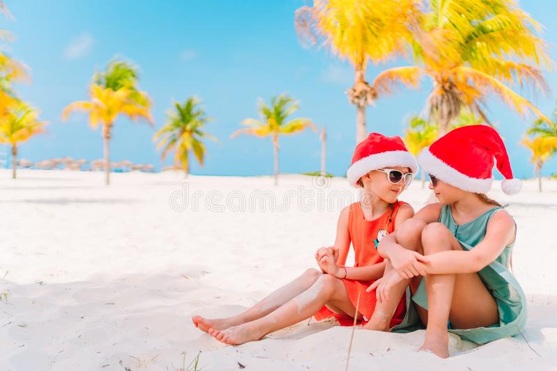 Little adorable girls in Santa hats during beach Christmas vacation having fun together. Little adorable girls in Santa hats having fun anad fooling at Christmas stock images