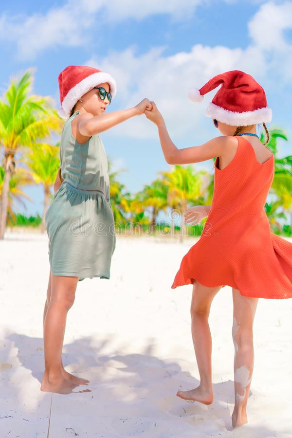 Little adorable girls in Santa hats during beach vacation have fun together royalty free stock photography