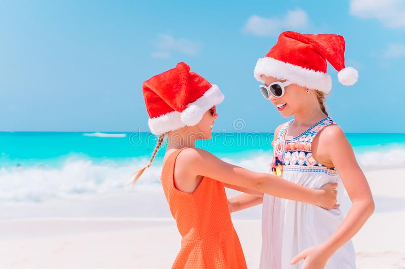 Little adorable girls in Santa hats during beach Christmas vacation having fun together. Little adorable girls in Santa hats having fun anad fooling at Christmas stock photo
