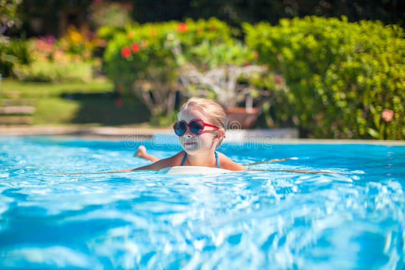 Little adorable happy girl swims in the swimming. Pool. This image has attached release royalty free stock photography