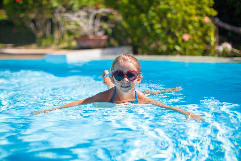 Little adorable happy girl swims in the swimming. Pool. This image has attached release royalty free stock image